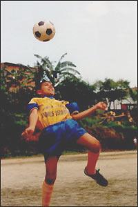 Un niño que participaba en el proyecto de las escuelitas de Andrés Escobar juega con el balón
