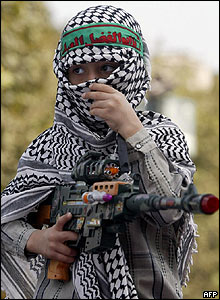 An Iranian boy wears a Palestinian scarf and holds a toy gun