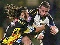 Leeds full-back Tim Stimpson is tackled by Paul Griffen