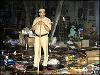 A police officer stands at the site of a blast in Sarojini Nagar market, Delhi