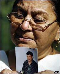 A woman cries holding a picture of her missing son Michael