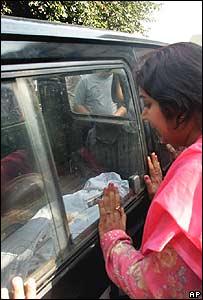 Un mujer observa a una de las víctimas de las explosiones.