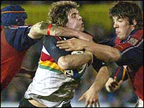 Dragons James Ireland is tackled by Alan Quinlan and Donncha O'Callaghan
