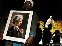 Thelma Mosley sostiene un retrato de Rosa Parks mientras espera poder entrar al Capitolio en Washington