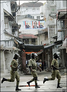 Policemen running through the Stone Town