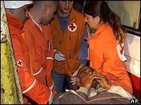 Paramedics carry an injured man after the blast