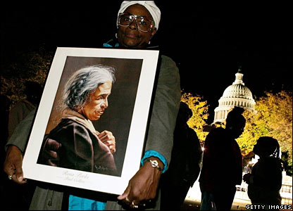 Thelma Mosley holds a portrait of Rosa Parks as she waits in-line to enter the US Capitol Rotunda to pay her respects