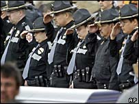 Police officers salute the casket of fellow officer Daryl Lussier
