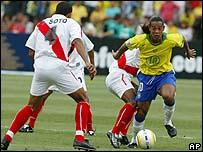 El brasileño Ronaldinho trata de pasar al peruano Soto.