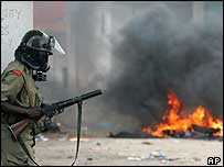 Zanzibar policeman looks at burning barricade