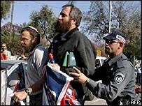 An Israeli policeman pushes settlers away during a demonstration outside the Knesset in Jerusalem