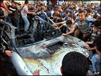 Palestinians gather around the wreckage of the car in Jabaliya refugee camp