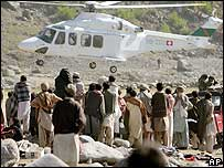 Survivors of the South Asian earthquake watch a relief helicopter land