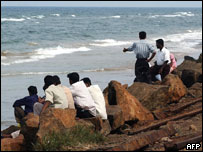 Sri Lankans look out at the sea, 29 March 2005, in Colombo