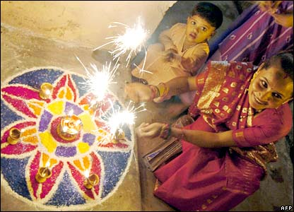 A woman and child wave sparklers in Karachi, Pakistan