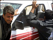 Iraqis weep by bloodied car of police officer shot dead in southern Iraqi city of Najaf