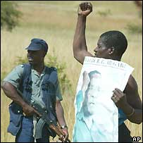 Police in Zimbabwe and a man holding up a poster of President Robert Mugabe