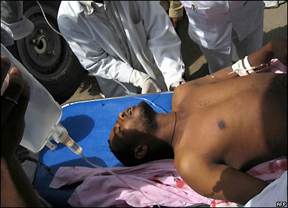 Man being carried into an Addis Ababa hospital with a drip