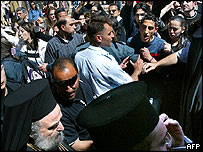 Palestinians protesters shout at the Greek Orthodox Patriarch of Jerusalem, Irineos outside the Church of the Holy Sepulchre