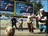 Niños iraquíes juegan al fútbol en la calle, frente a carteles publicitarios sobre las elecciones