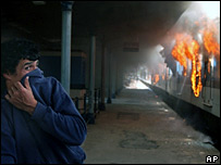 A man covers his face as he passes in front of a burning train at the Haedo station outside Buenos Aires