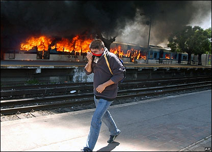 A man covers his face as he passes in front of a burning train