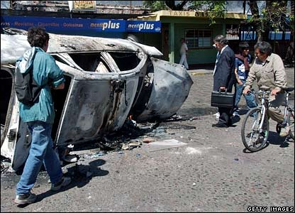 People observe a burned police car at Haedo station