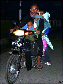 An Indonesia family leaves home to get to higher ground in Aceh