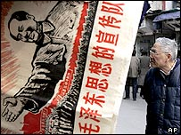 """A man looks at antique shop near a reproduction of a propaganda poster from Cultural Revolution era with Chinese characters read 'Maoism Propaganda Corps """" Thursday March 10, 2005 in Shanghai, China."""
