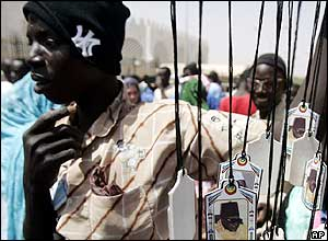 Man walks past a stall selling Mouride pendants