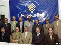 "Egyptian Muslim Brotherhood candidates for parliamentary elections pose in front of the slogan: ""Islam is the solution"""