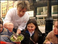 Jamie Oliver serving food to schoolchildren