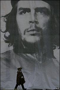 Un indígena Mapuche de Chile caminando y en el fondo un póster gigante del Che Guevara