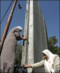 Palestinian women climb through the West Bank barrier at Abu Dis