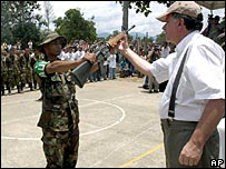 Colombia's Peace Commissioner, Luis Carlos Restrepo, receives a weapon from an AUC fighter