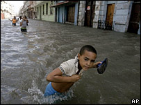 A boy walks in a flooded street in Havana, Cuba