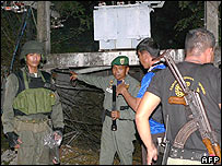 Thai soldiers inspect the damage to electrical poles cause from a bomb that exploded in the southern Thai province of Narathiwat, late 02 November 2005.
