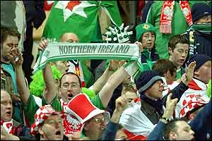 Northern Ireland's fans sing and wave flags as their team play Poland in Warsaw