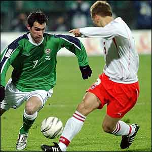 Northern Ireland's Keith Gillespie (L) battles for the ball with Poland's Tomasz Rzasa during the World Cup qualifying match at Wojska Polskiego Stadium, Warsaw