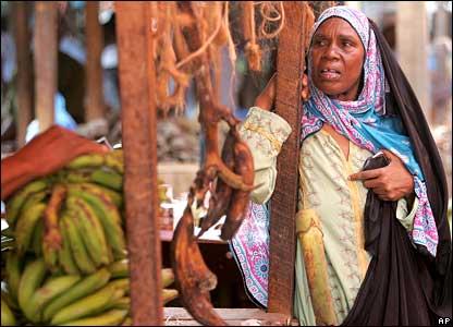 A woman buys bananas in a market in Stone Town, Zanzibar