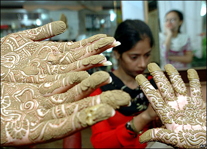 Girls in Pakistan show their hands, painted with henna ahead of Eid