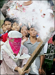 A blindfolded Filipino girl hits a clay pot filled with candies and powder during Eid games