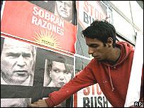 Un trabajador coloca un póster en protesta de Bush en Mar del Plata