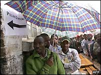 People in Zimbabwe waiting to vote under umbrellas