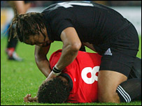 Tana Umaga comes to the aid of a stricken Colin Charvis
