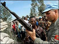 UN peacekeeper holding gun handed over by Congolese militiaman