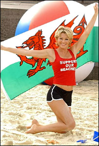 Model Nell McAndrew with Welsh flag on beach, publicising the new guide