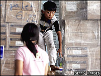 Children from the Island of Nias made homeless play amongst crates of international aid as they arrive in Medan April 1, 2005