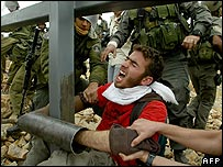 Israeli border police try to remove a demonstrator locked to a pole in Bilin.