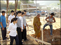 Chitladda and members of her family watch as a monk blesses the foundations of the new complex